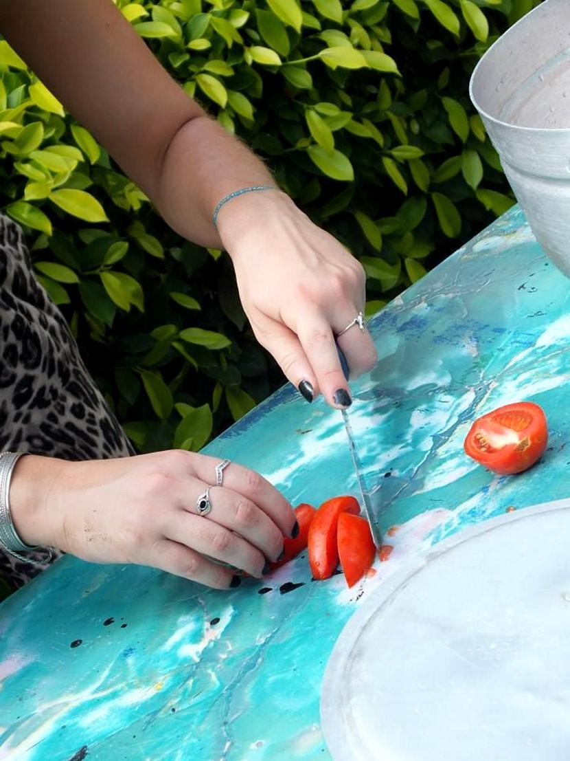 Una volontaria taglia i pomodori