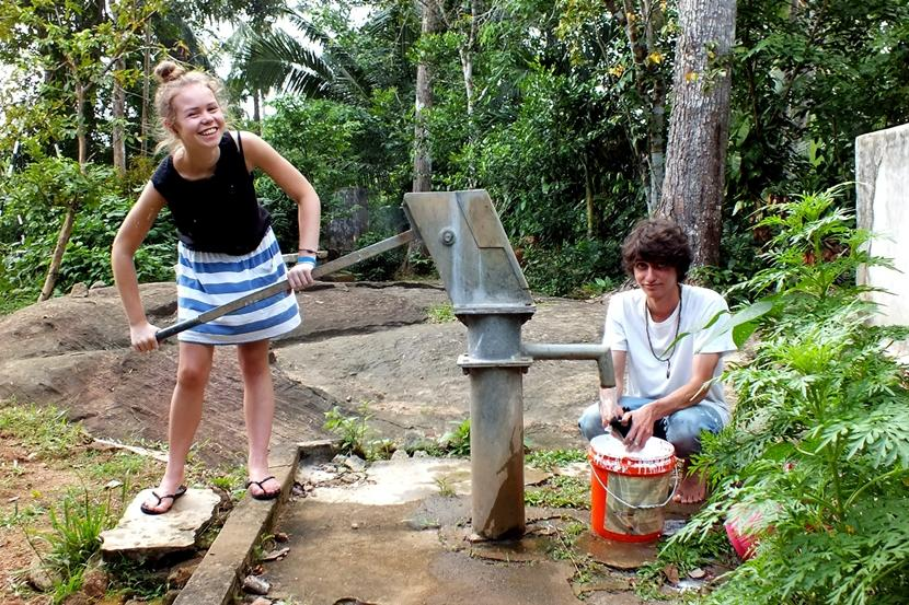Due volontari di Projects Abroad prendono acqua da un pozzo in Sri Lanka
