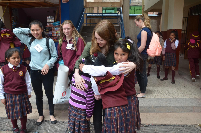 Una giovane volontaria riceve un abbraccio dai bambini di una scuola di Cusco, Perù