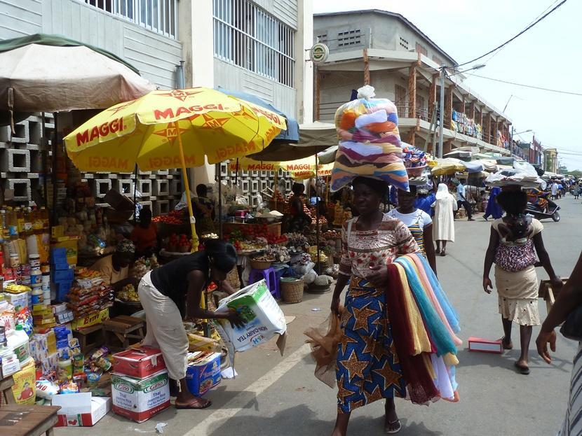 トーゴの市場で頭に物を載せて歩く女性