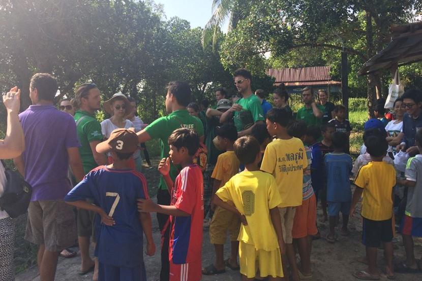 Lokale kinderen krijgen uitleg van de vrijwilligers over een schoonmaak actie in het dorp