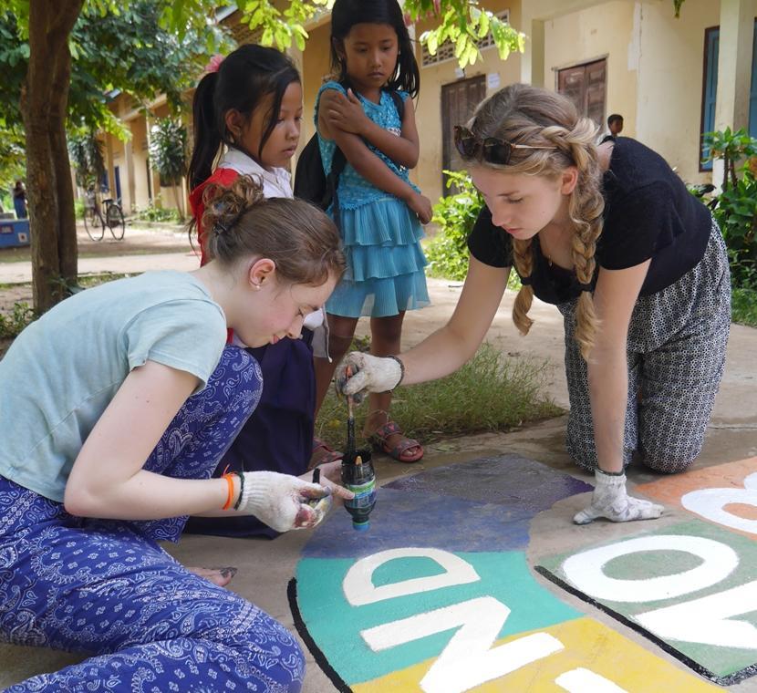 Het schoolplein wordt door vrijwilligers van de Sociaal & Samenleving jongerenreis naar Cambodja voorzien van educatieve schilderingen.