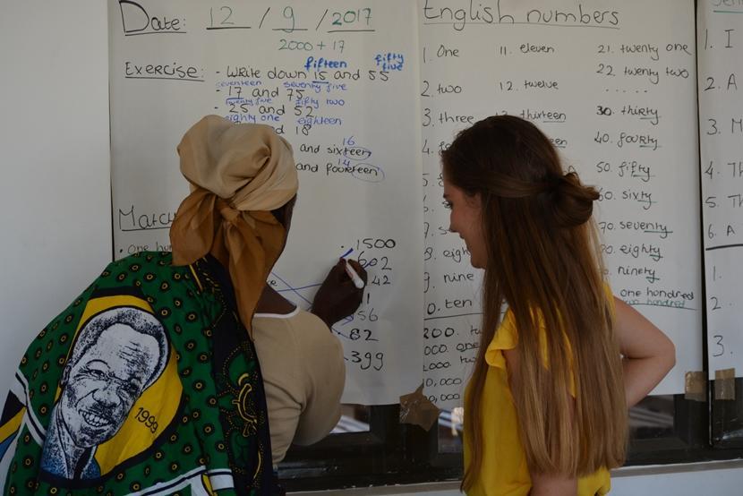 Vrijwilliger Claire helpt een deelnemer van het microkrediet project bij haar oefening in getallen.