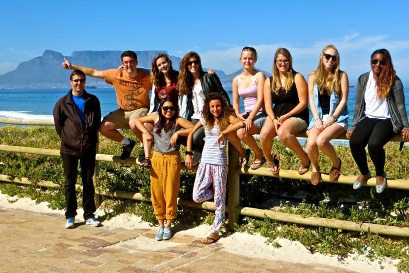 Een groep vrijwilligers van de jongerenreis naar Kaapstad poseren op het strand met de Tafelberg in de achtegrond.