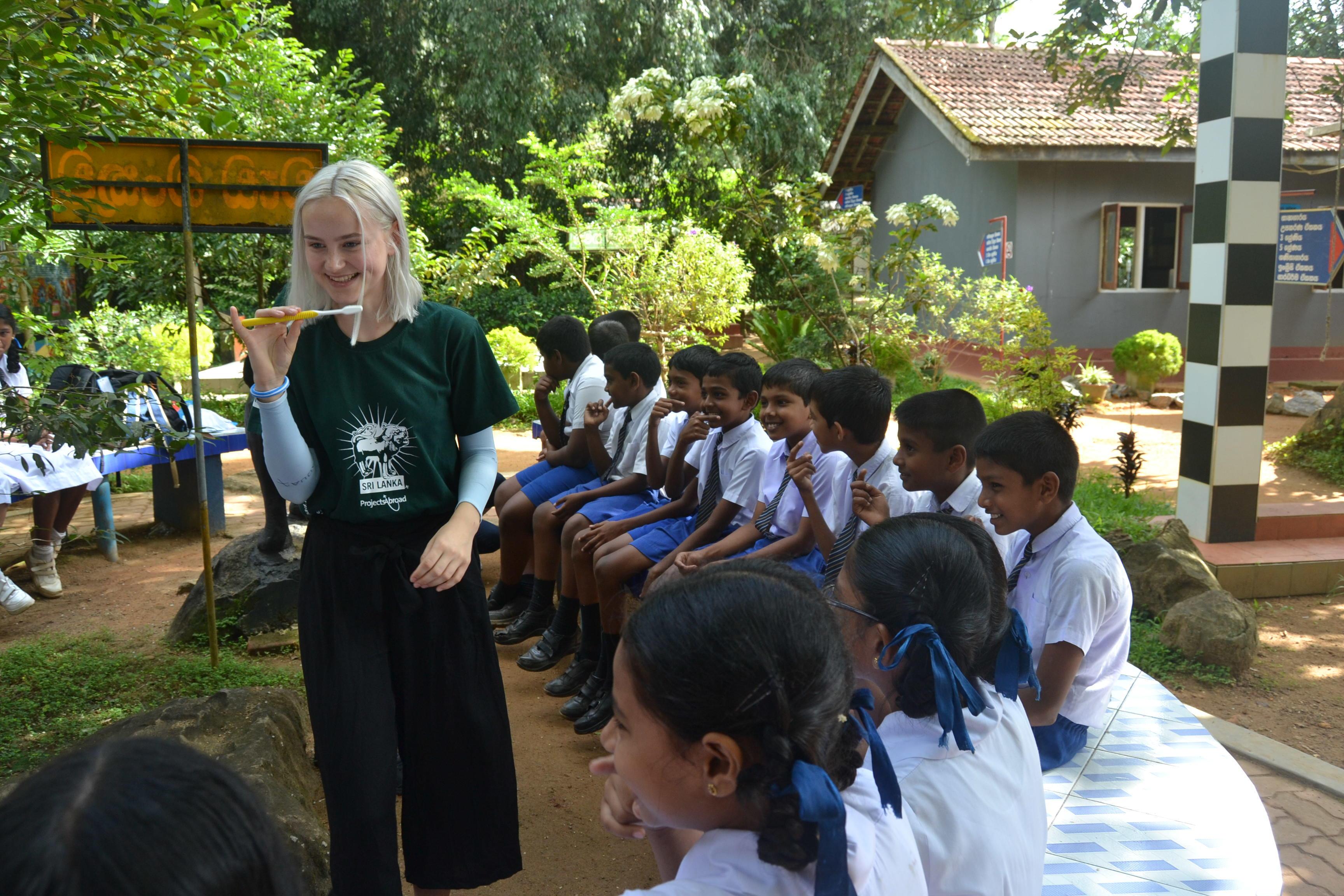 Een jongerenreis deelnemer geeft voorlichting over tandheelkunde in Sri Lanka.