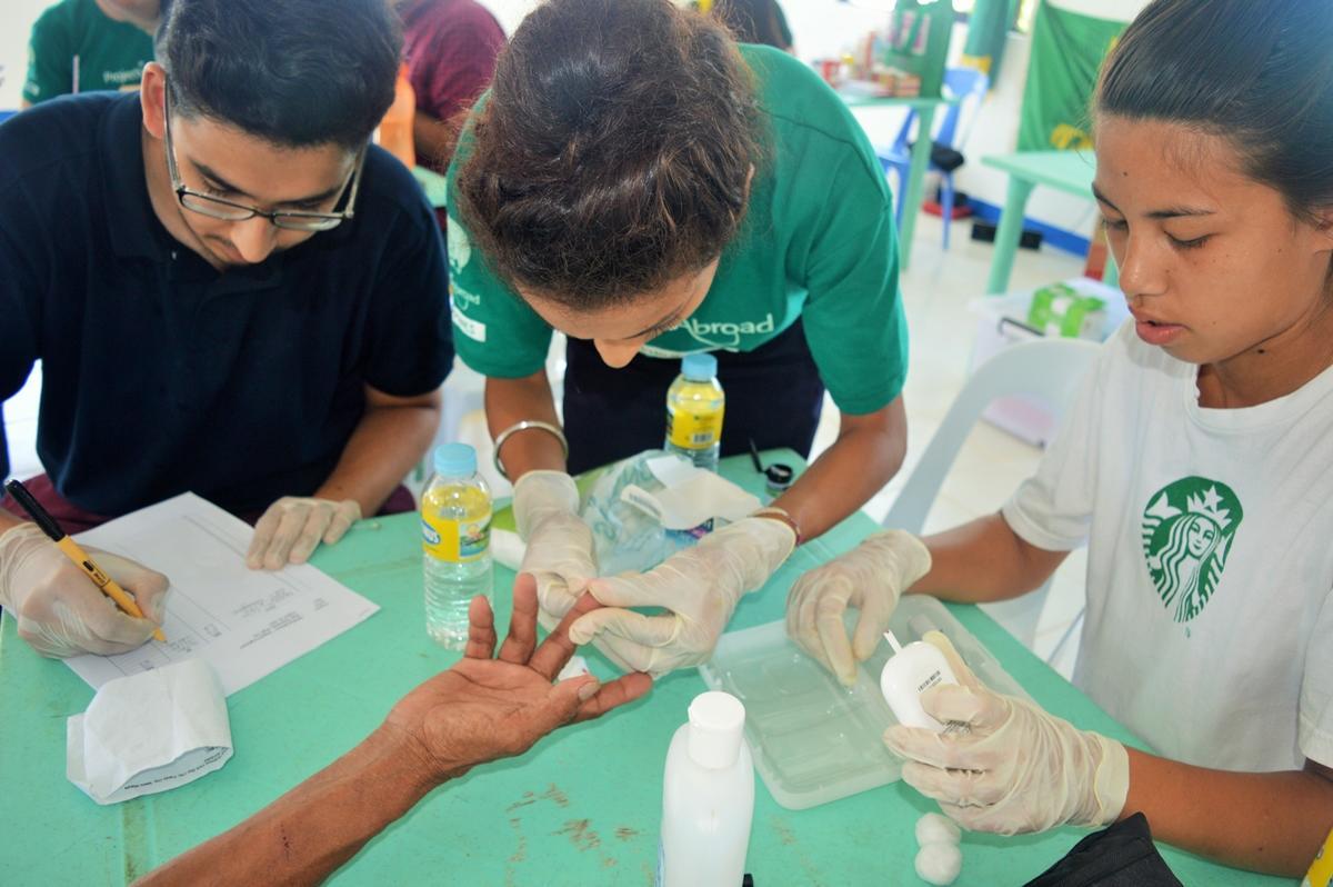 : Een glucose test wordt uitgevoerd door een vrijwilliger tijdens een medische outreach in de Filippijnen
