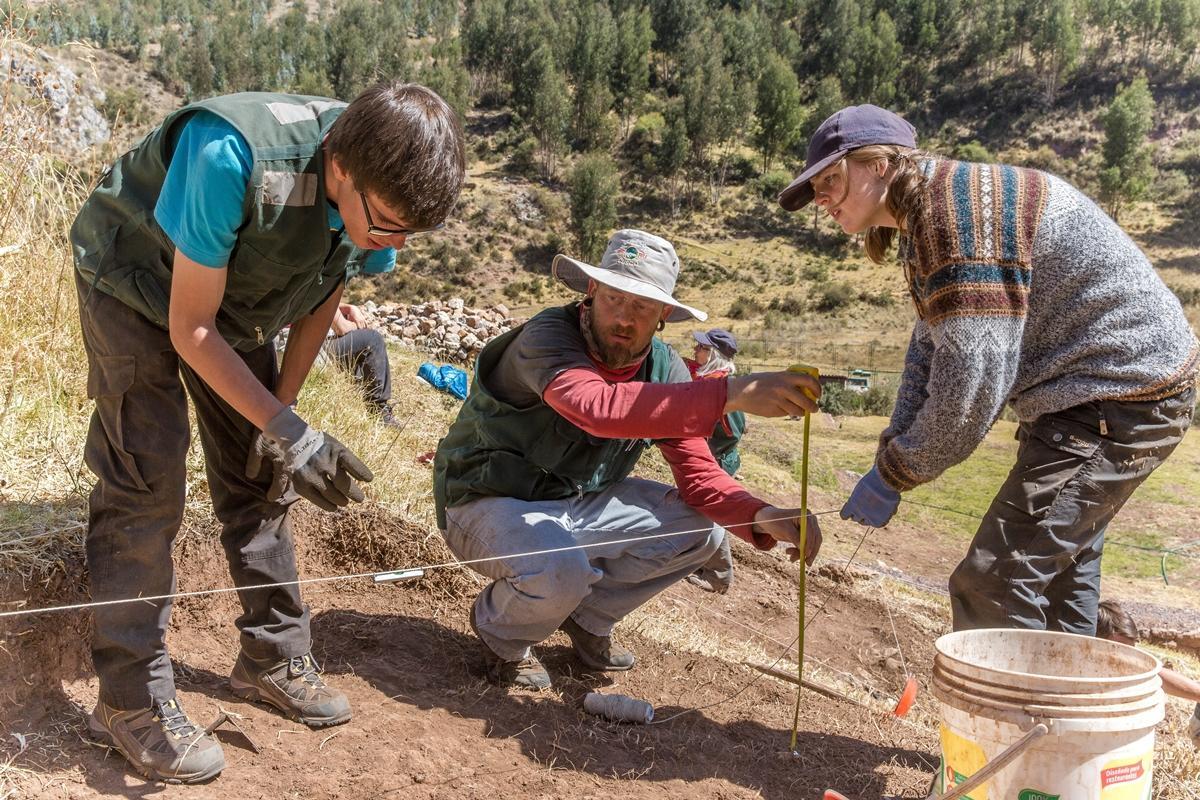 In Peru werken twee vrijwilligers op het terrein van Sacsayhuaman om de diepte van de afgravingplaats te meten.