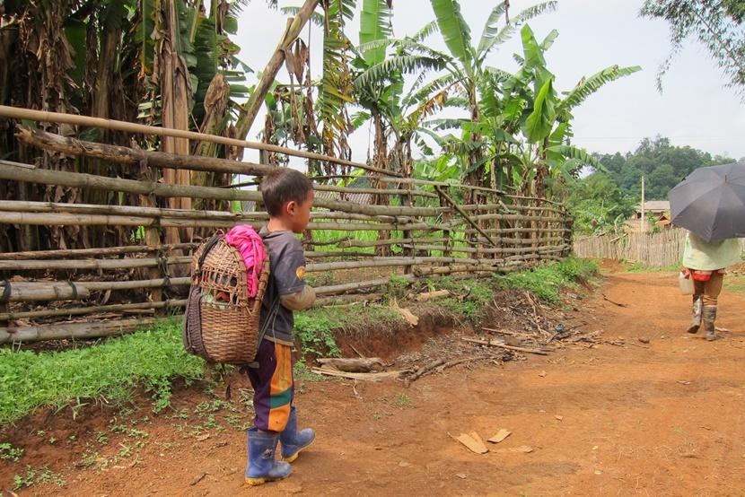 Laos boy walking down road with backpack