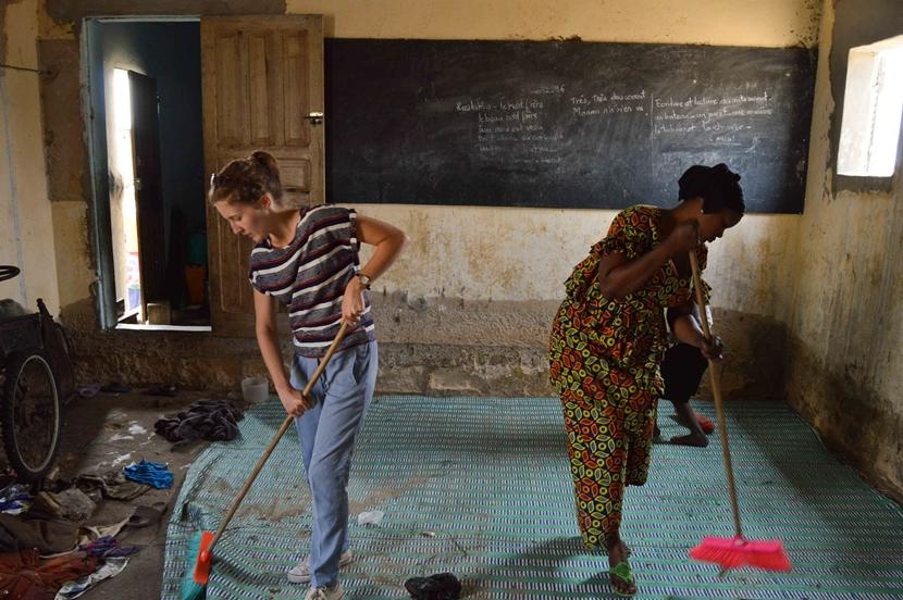 A Belgian Projects Abroad volunteer works with local staff to help clean a daara where talibé children sleep in Saint Louis, Senegal