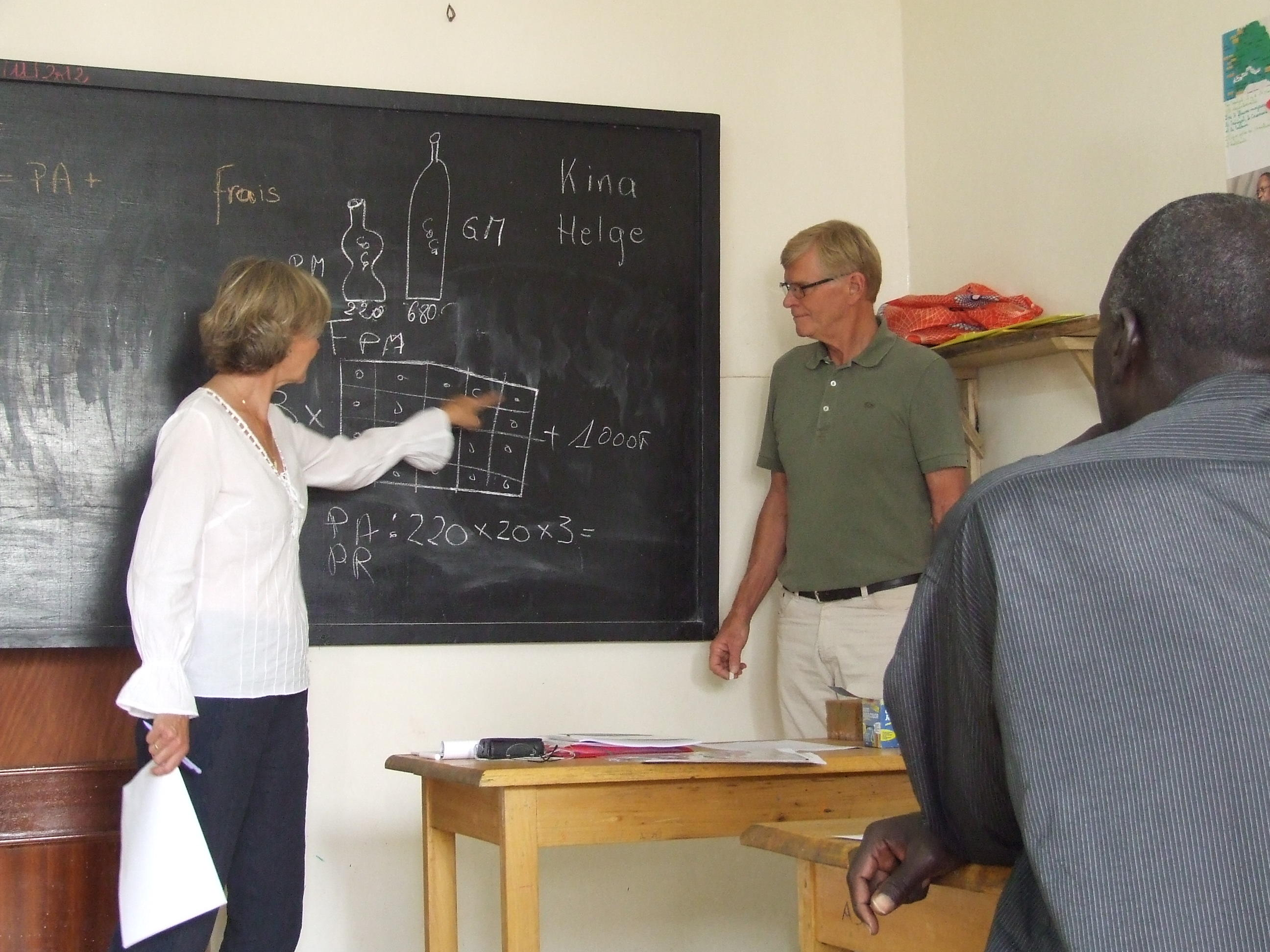 Students in Africa attend a maths class taught by older adults volunteering abroad on a Micro-finance Project.