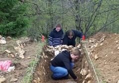 Projects Abroad Archaeology volunteers investigate a trench at an excavation site in Romania.