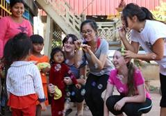 Volunteers and local children play with bubbles during recess at a day care centre in Cambodia.