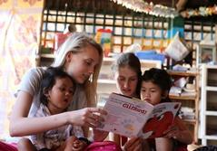 Young students volunteering with Projects Abroad Cambodia read with the children at a daycare center.