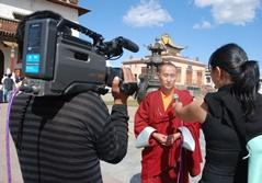 Journalism intern and camera crew interview a monk at a temple in Ulaanbaatar, Mongolia.