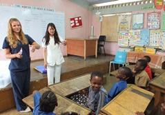 Two female volunteers giving a presentation to school children in a medical outreach program in Jamaica