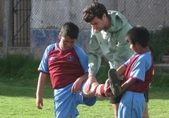 Male sports volunteer on a project in the Sacred Valley of Peru coaching after school soccer to students