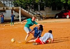 A volunteer sports coach plays soccer with students at a local school in Ghana, West Africa.