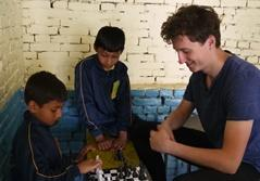 Projects Abroad Teaching volunteer plays chess with two young boys at Deepmala's English camp during a school break in Nepal.