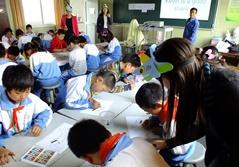 A volunteer teacher helps students with an activity during her lesson at a school in China, Asia.