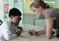 A volunteer teacher in Cambodia works one-on-one with a student during class.