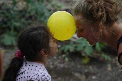 Una volontaria e una bimba giocano con un palloncino