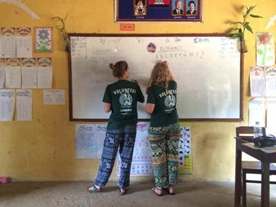 Projects Abroad Cambodia conservation volunteers write the alphabet on a whiteboard during English classes at a local primary school, where they also help to develop educational games for the children.