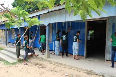 Projects Abroad Marine Conservation volunteers paint a school building blue as part of a community day
