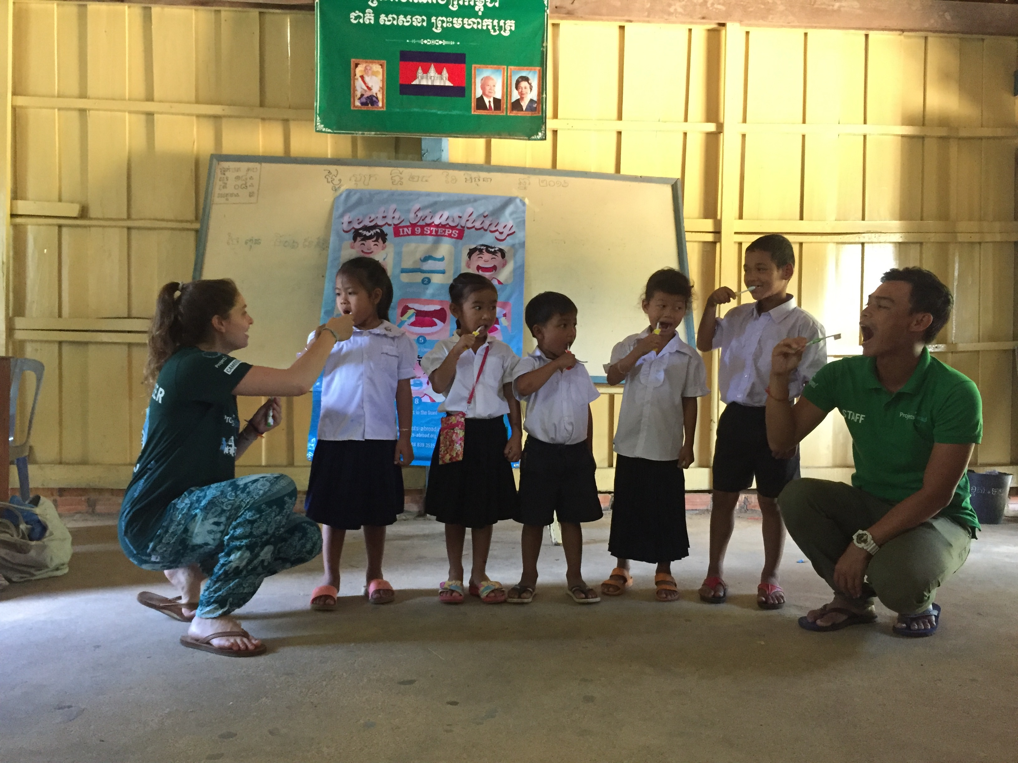 A volunteer and staff show the kids how to brush their teeth