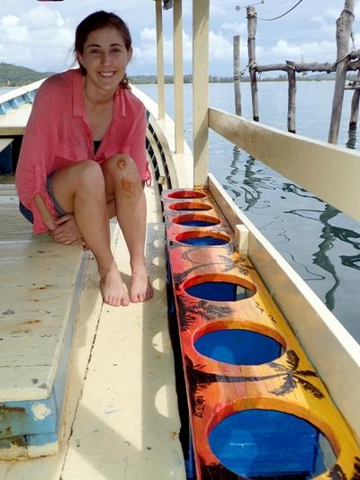 Projects Abroad Marine Conservation volunteer, Kate Jackson from Australia, paints the boat used for dives at her placement in Cambodia