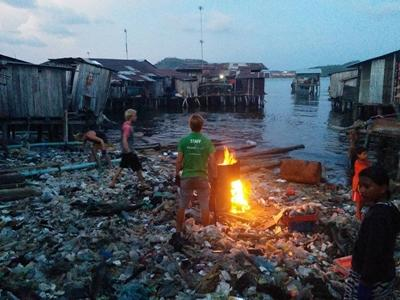 Staff and volunteers burn trash with local children