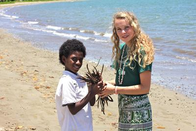 Projects Abroad conservation volunteer takes part in a beach clean up with a local boy in Fiji
