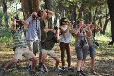 A group of Projects Abroad conservation volunteers pose with binoculars during a walk through Wild at Tuli Nature Reserve in Botswana