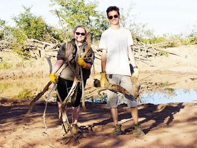 A group of Projects Abroad volunteers do waterhole maintenance at their conservation project in Wild at Tuli reserve, Botswana.