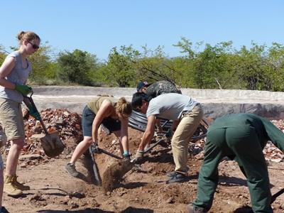 Volunteers work on the piping to the waterhole in Botswana