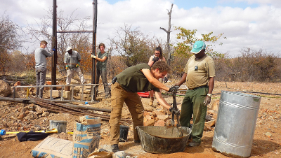 Volunteers and staff installing the solar pump