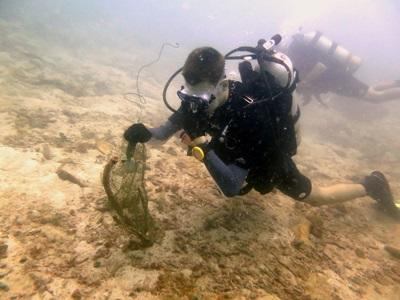 Projects Abroad Marine Conservation volunteer takes part in a Dive Against Debris, collecting rubbish left by tourist boats