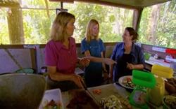 A volunteer shows Sue and Julie how to prepare food for the animals