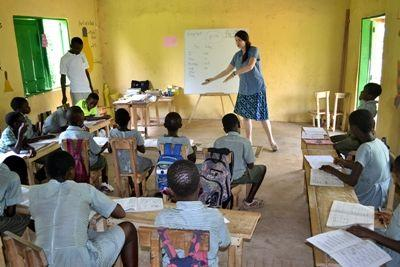 A Projects Abroad volunteer teacher leads a class for young Ghanaian students learning English.