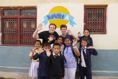 Malte and Harry wave with school children at Deepmala's English camp in Nepal, where they taught English, drama, sport, and craft activities.