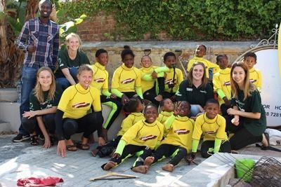 Projects Abroad Nutrition interns sit with children from the Surfing project in Cape Town, South Africa