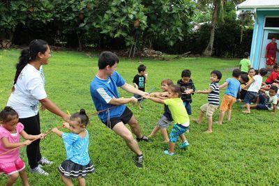 Ein Freiwilliger von Projects Abroad spielt Tauziehen mit kleinen Kindern in Samoa