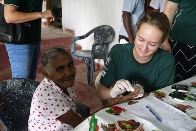 Projects Abroad Freiwillige des Medizinprojekts testen Blutzucker und Blutdruck beim Außeneinsatz außerhalb von Colombo