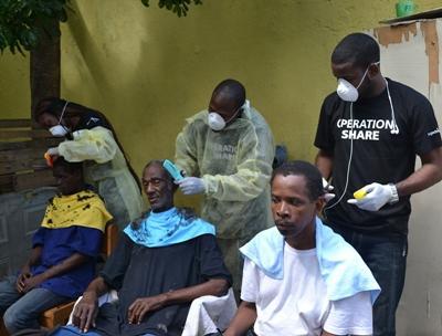Projects Abroad Freiwillige und Mitarbeiter bieten einen Friseurdienst für Obdachlose Männer beim Welt Obdachlosen Tag am 10. Oktober 2015 an
