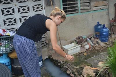 Projects Abroad Freiwillige zeigen örtlichen Familien die praktische Anwendung des Larvizids in ihren Häusern mit dem Ziel der Verbreitung des Dengue Virus vorzubeugen.
