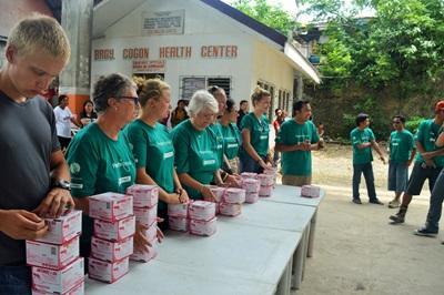 Projects Abroad Freiwillige verteilen Kisten mit Larviziden an Bewohner während einer Kampagne zur Bekämpfung des Dengue Virus auf den Philippinen.