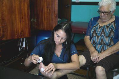 Eine ältere Frau bekommt von einer Projects Abroad Freiwilligen eine Elektrodenbehandlung am Fuß im Asociacion Centro de Atención al Anciano Francisca Valerio Badilla