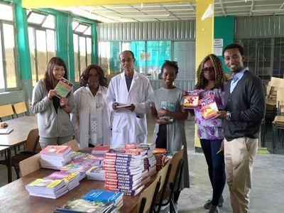 Projects Abroad Mitarbeiter und Freiwillige überreichen die Spende von Lehrbüchern und fiktionalen Büchern dem Direktor der Berhane Zare Schule in Addis Abeba, Äthiopien.
