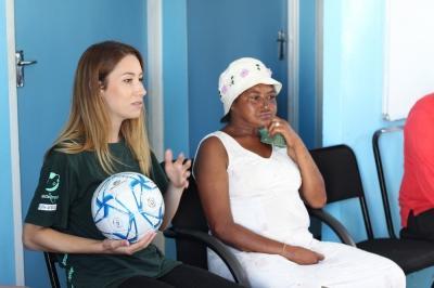 Ein Freiwilliger aus dem Ernährung - Projekt sitzt zusammen mit einem Mitglied der Gemeinde beim Outreach Programm in Kapstadt, Südafrika.