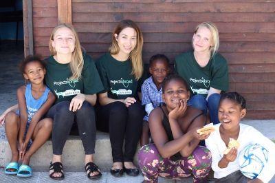 Projects Abroad Freiwilliger aus dem Ernährungs – Projekt sitzen zusammen mit einer Gruppe von Mädchen an ihrem Einsatzort in Kapstadt, Südafrika