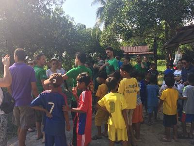 Dorfkinder bereiten sich mit Freiwilligen auf eine Müllsammelaktion im Ort vor